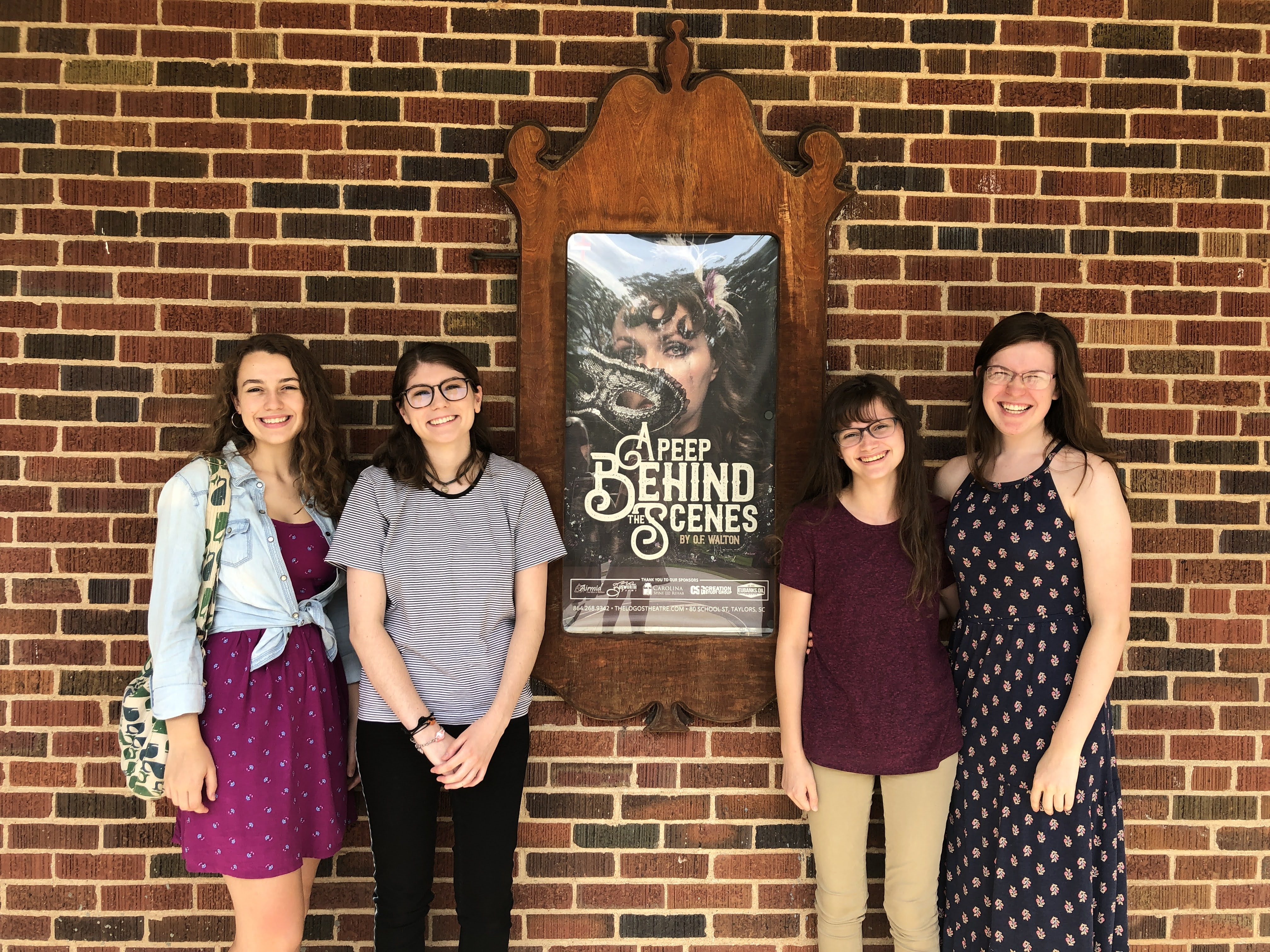 Four girls standing in front of a brick wall of the Logos Theatre, around a poster of the play A Peep Behind the Scenes